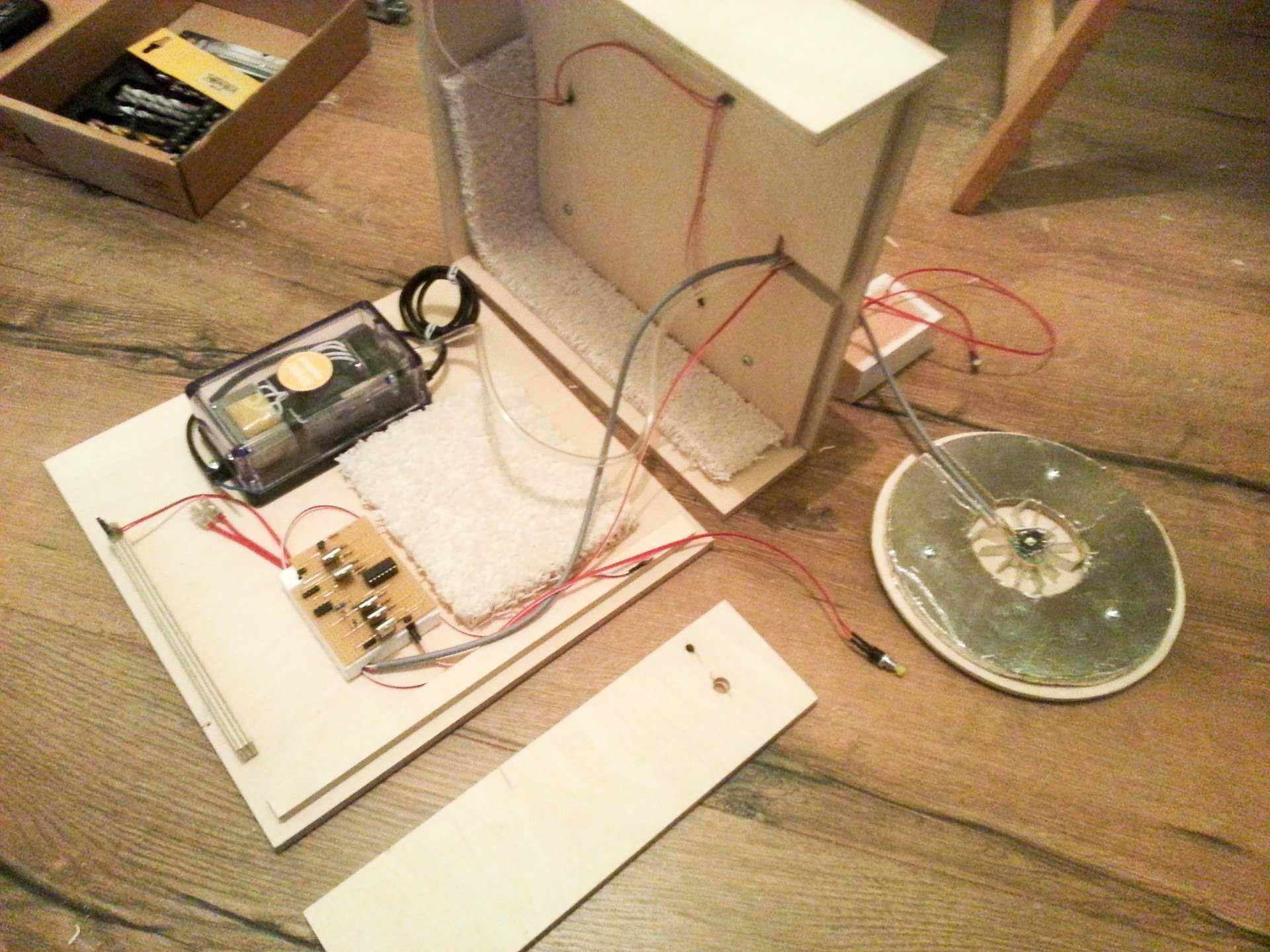 Eine Holzkiste ist aufgeklappt, darin ist Elektronik verbaut.