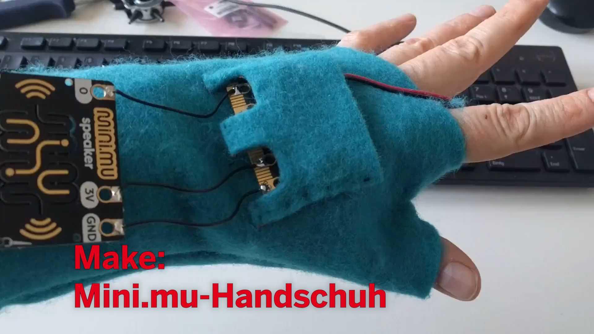 Hand mit Handschuh aus Filz und aufgenähtem Mikrocontroller.