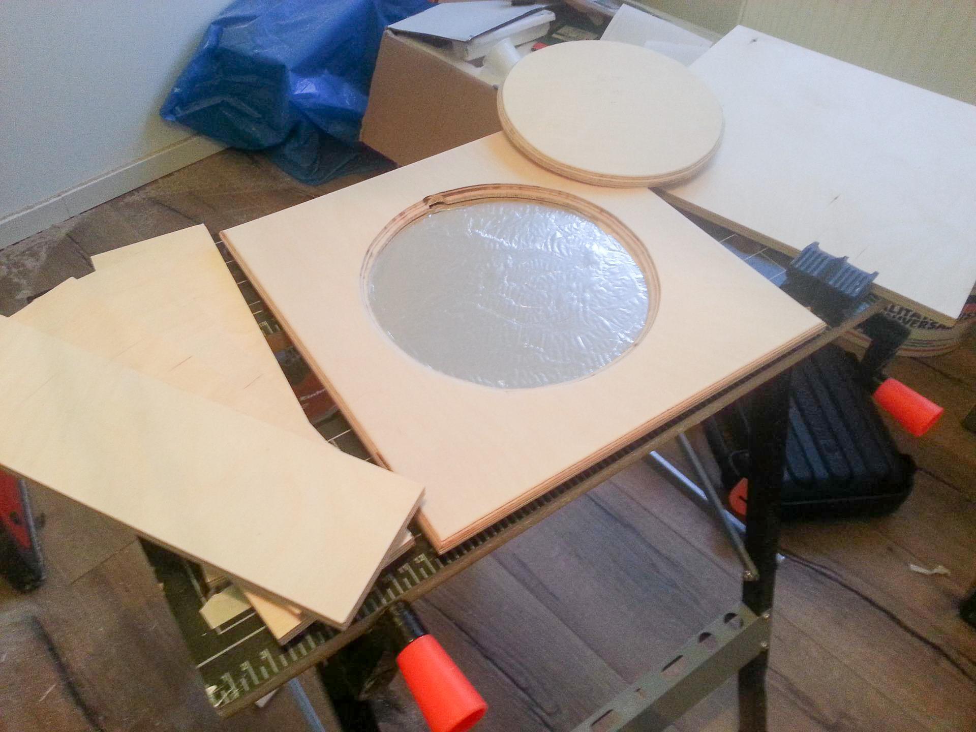 Ein quadratisches Stück Holz mit einem runden Loch in der Mitte. Darunter glänzt es metallisch