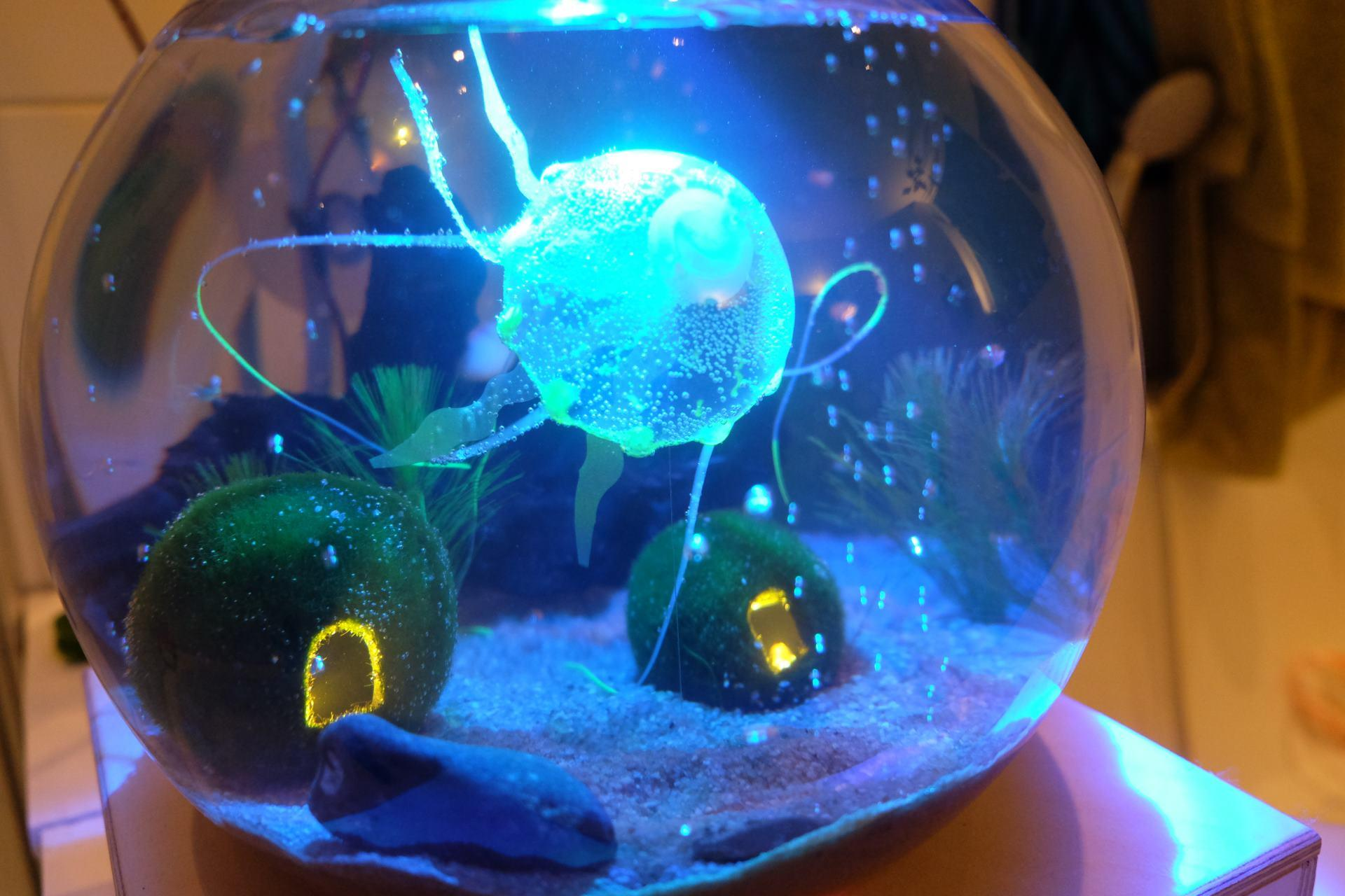 In einer runden Glaskugel leuchten eine blaue Qualle und zwei kleine kleine Häuschen