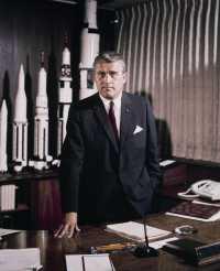 Wernher von Braun steht hinter Schreibtisch
