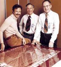 Die Intel Trinity (von links: Andrew Grove, Robert Noyce, Gorden Moore) beim 10-Jahres-Jubiläum vor einem Layer vermutlich des 8080-Prozessors