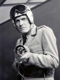 Schwarz-Weiß Foto eines Mannes in Uniform und Helm mit Waffe