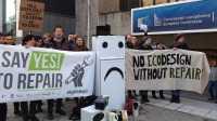 Vor einem Gebäude der Europäischen Kommission protestieren Menschen mit Plakaten für das Recht auf Reparatur