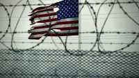 Stacheldraht, dahinter flattert beschädigte US-Fahne