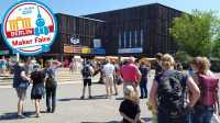 Blick auf das FEZ Berlin bei strahlendem Sonnenschein und blauem Himmel: Verschiedene Menschen laufen auf das FEZ zu.