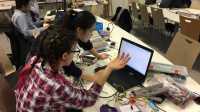 Zwei Studentinnen sitzen vor einem Latop und weiterer Hardware.