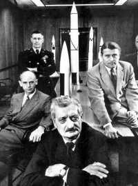Hermann Oberth (vorne mitte) entwickelte die Grundlangen der Raumfahrt, arbeitete für die Nazis an der V2 und für die Amerikaner in der Raketenforschung. Auf dem Foto außerdem: Ernst Stuhlinger, im Dritten Reich in der Atomenergieforschung und im Peenemünder Raketenprogramm, später in den USA führend in der US-Raketenforschung (links, sitzend); US-Generalmajor Holger Toftoy vom US-Raketenprogramm (hinten stehend) und Wernher von Braun, ebenfalls Mitentwickler der V2 und einer der führenden Köpfe des US-Raumfahrtprogramms bis hin zur Apollo-Rakete Saturn V (rechts, sitzend).