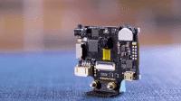 Ein kleines Schwarzes Board auf einem 3D-gedruckten Adapter.