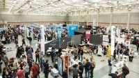Blick in eine Halle mit vielen Menschen und Ständen während der Maker Faire Hannover 2019.