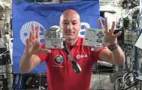In der Raumstation ISS fliegen zwei silberne Gehäuse, in denen Raspberry Pis eingebaut sind, vor einem Astronauten und der ESA-Flagge durch die Luft.