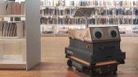 Ein schwarzer Kasten mit Rollen, vorn sind große Kugelaugen befestigt, im Hintergrund sind viele Bücherregale zu sehen.
