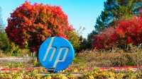 HP-Logo, dahinter herbstlich-bunte Bäume