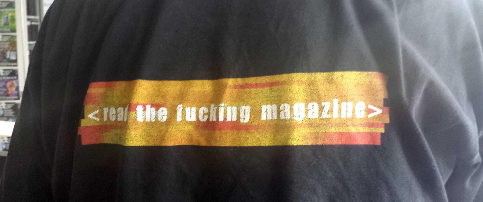 Mahnend steht es auf dem T-Shirt des Kollegen: Read The Fucking Magazine.