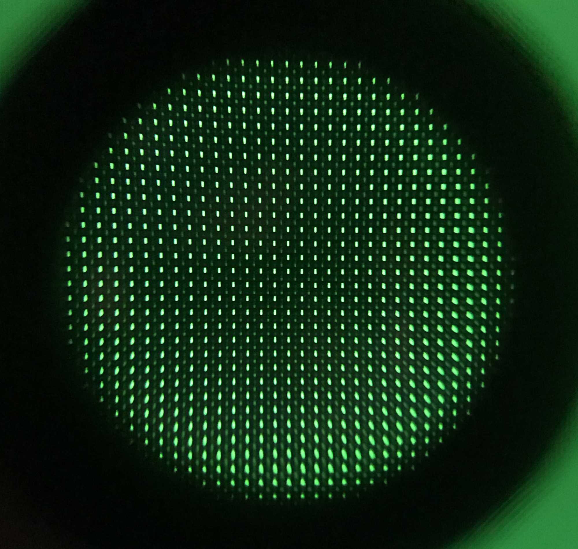 Unterm Mikroskop sieht man die grünen Pixel des VA-Panels, jeweils vier bilden ein Cluster: Das Pixel links oben leuchtet hell, eins nur schwach (rechts unten) und zwei sehr schwach (rechts oben und links unten). Die blauen und roten Subpixel in den vier Bildpunkten sind komplett aus.