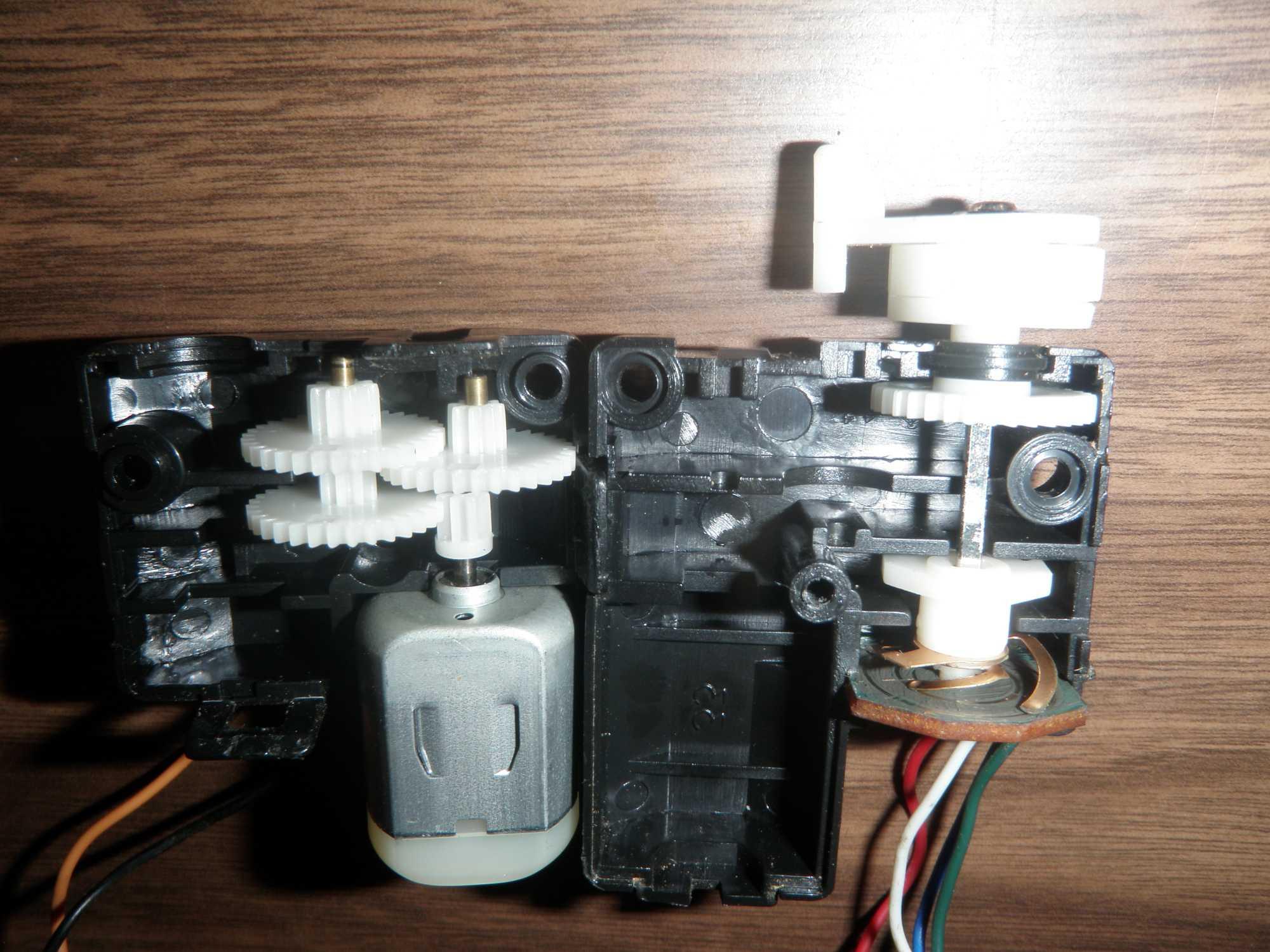 Ein einfacher Servo-Motor besteht aus einem Gleichstrommotor (links unten), einem Zahnradgetriebe (rechts oben) und einem Poti (rechts unten). Die Kontrolllogik ist auf dem Bild nicht abgebildet.