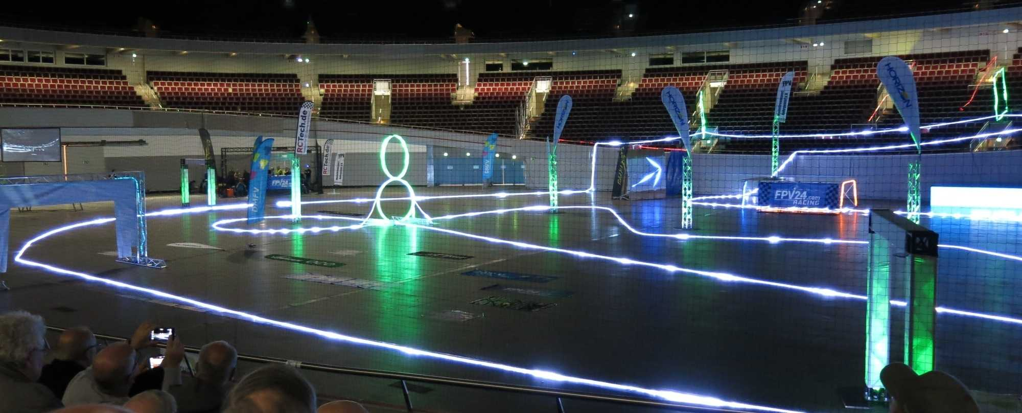 Wettkampfarena des INTERcopter Racing Cup 2017 in der abgedunkelten Halle mit illuminiertem Parcour