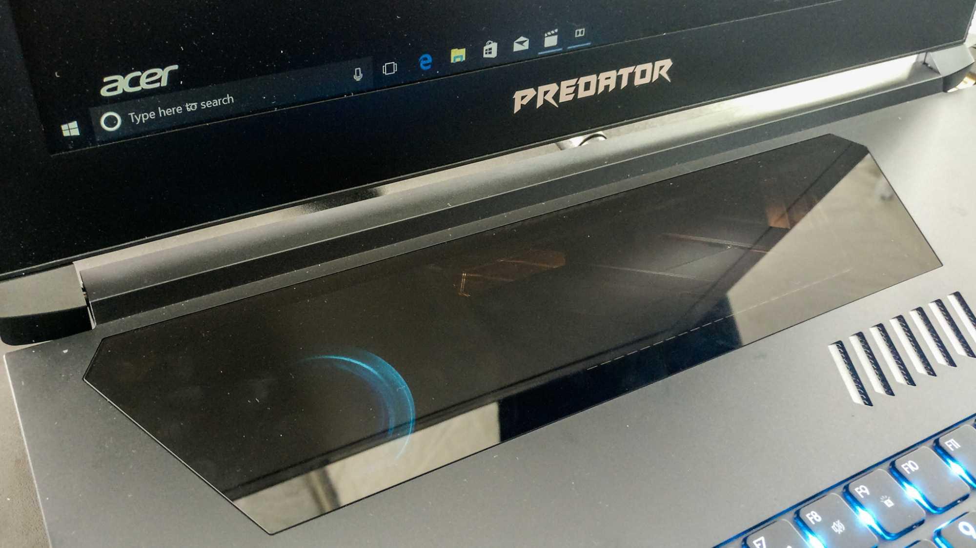 Nur ein mittlerer, trapezförmiger Bereich der Abdeckung dient als Touchpad, markiert durch eine gestrichelte Linie.