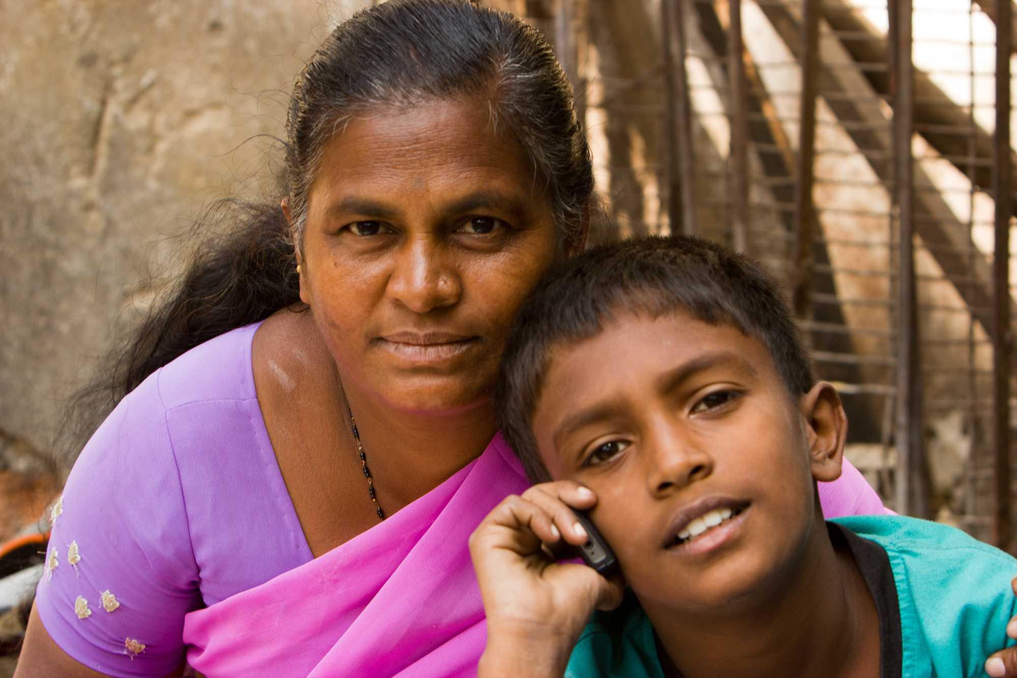 Indische Frau, davor Knabe, der mit Handy telefoniert