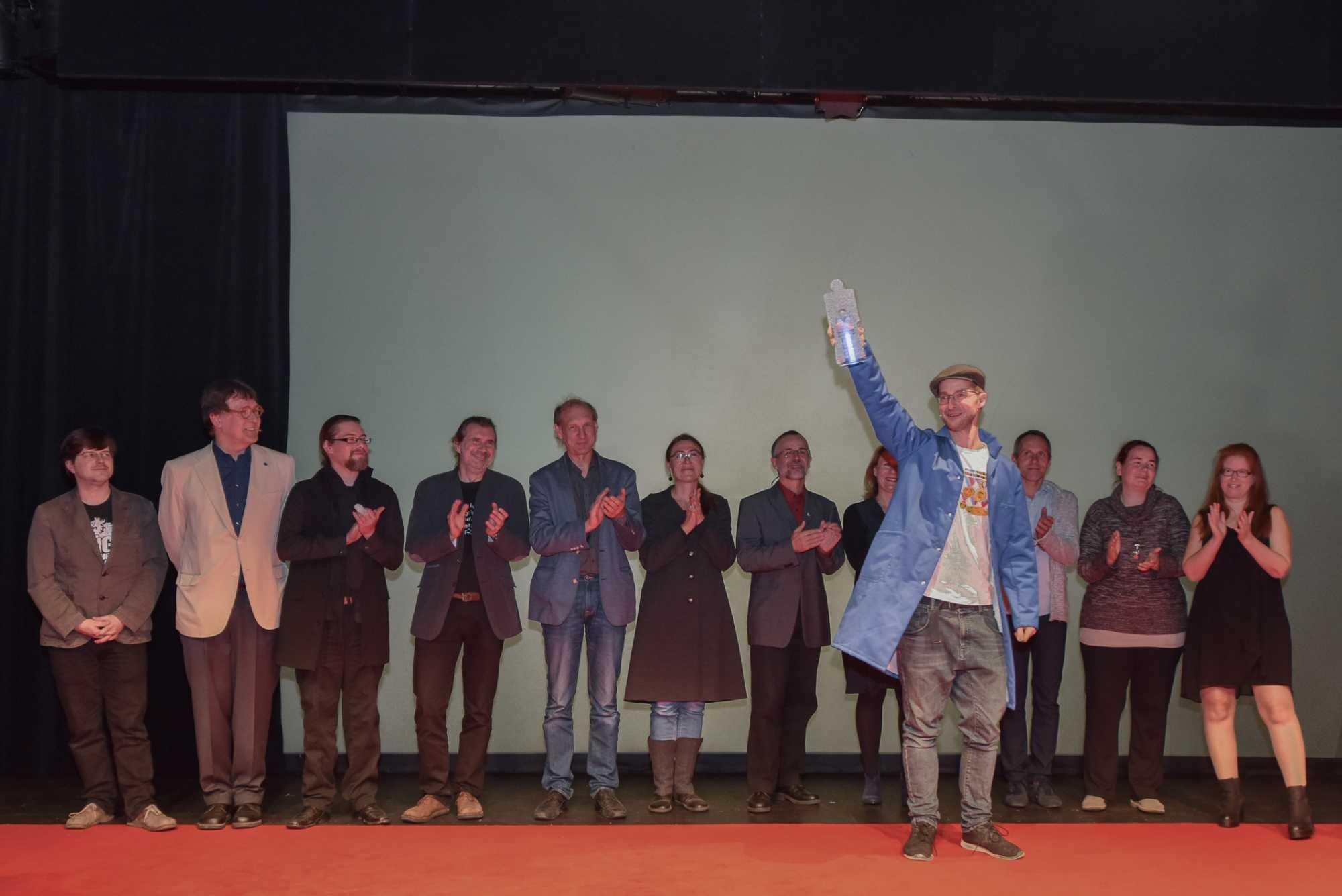 Eine Menschenreihe auf einer Bühne, davor ein Mann, der eine Betonfigur in die Höhe streckt