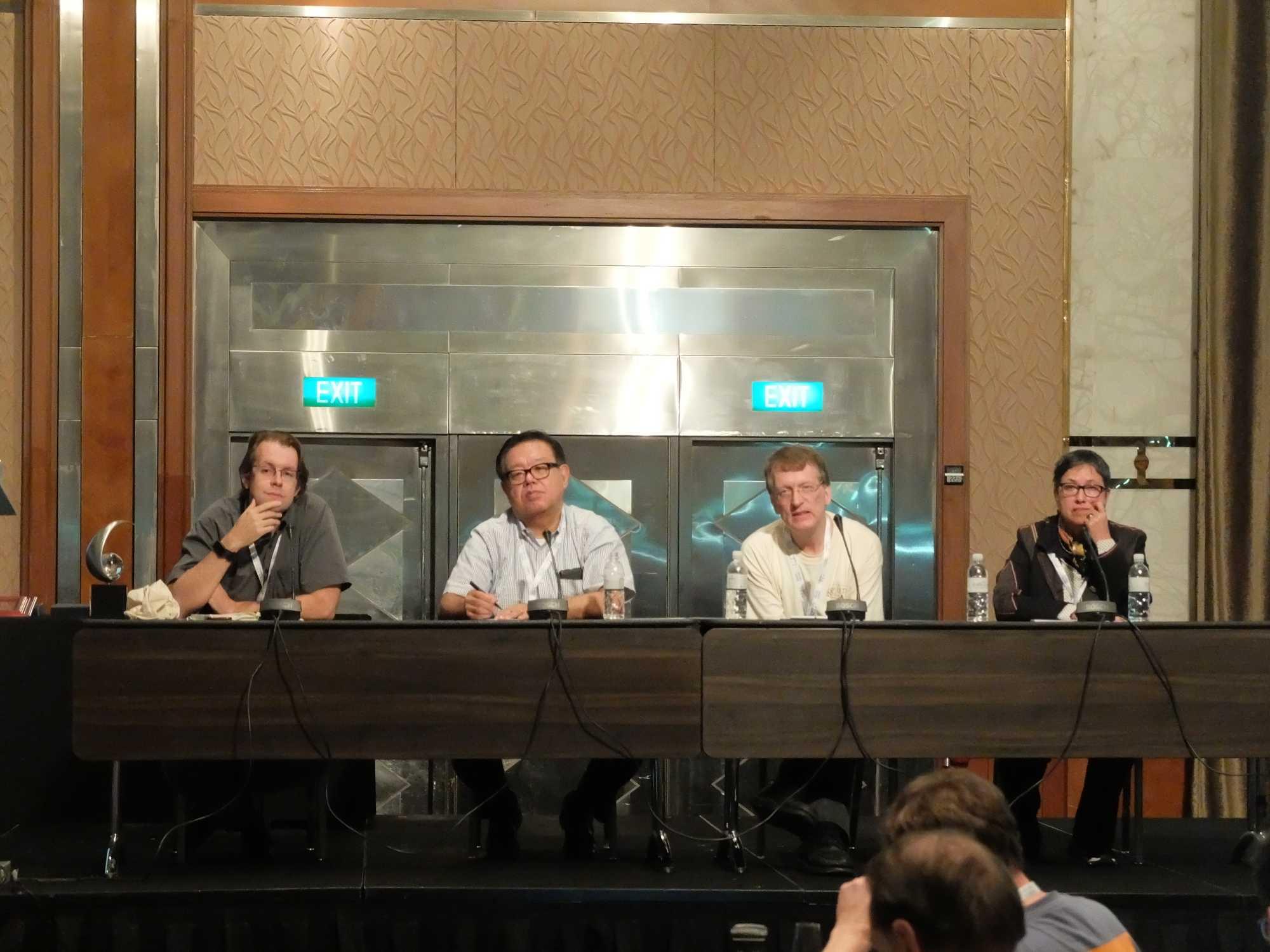 Dunkler Ausblick vor hellem Hintergrund: Brian Trammell, Jun Murai, Henning Schulzrinne und Monique Morrow beim 100. IETF-Treffen.