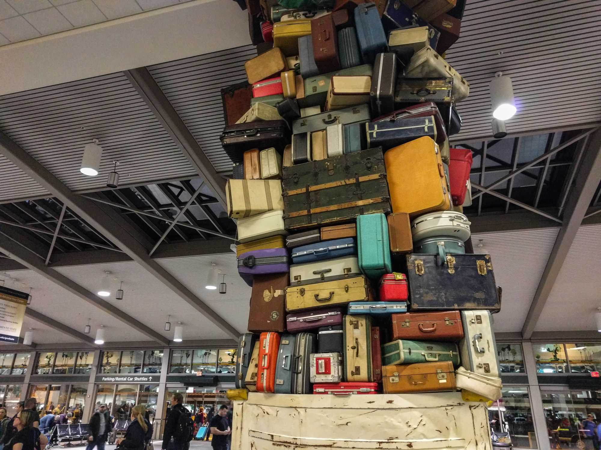 Bis zur Decke aufgetürmte Koffer in einer Flughafenhalle