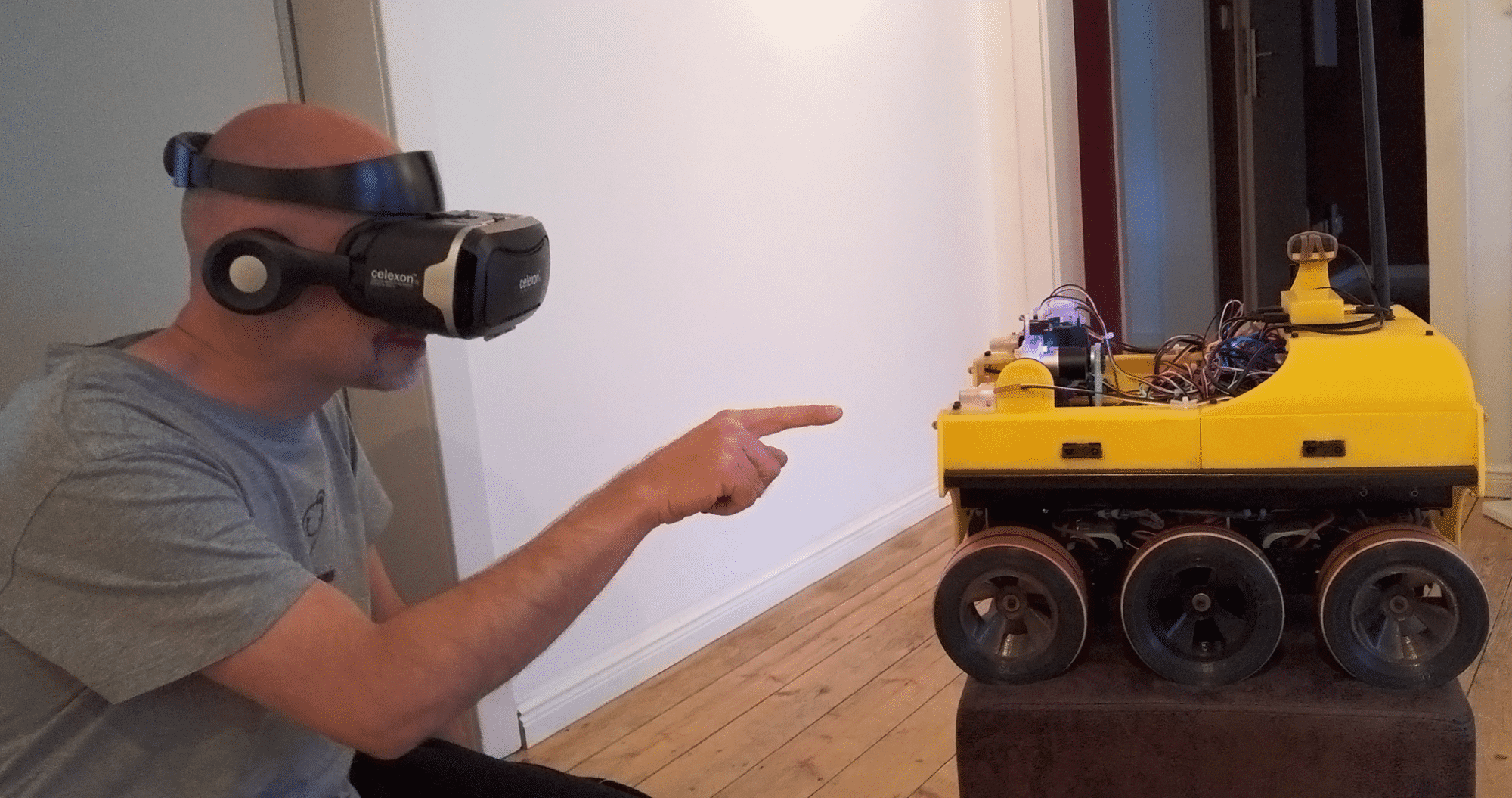 Ein Mann mit VR-Brille zeigt auf einen gelb-schwarzen Roboter