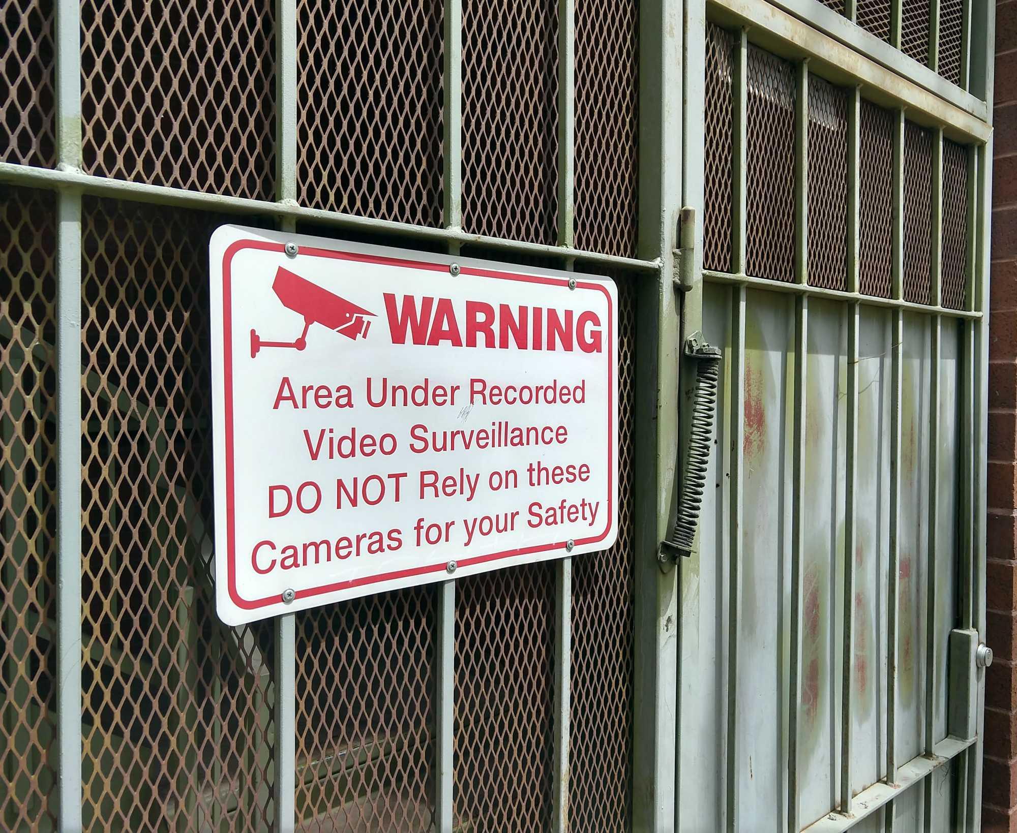 Warnschild: Personen sollen sich nicht auf die Überwachungskamera verlassen