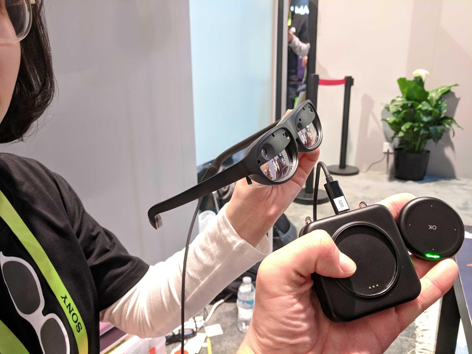 Die Nreal Light wird über einen kleinen Controller-Puck bedient (rechts), daneben ist die Recheneinheit zu sehen.