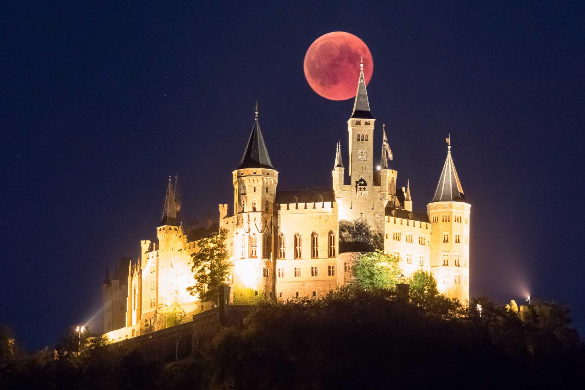 Wolkenfreier Himmel über dem Horizont ermöglichten es den Mond hinter der Burg Hohenzollern zu fotografieren.