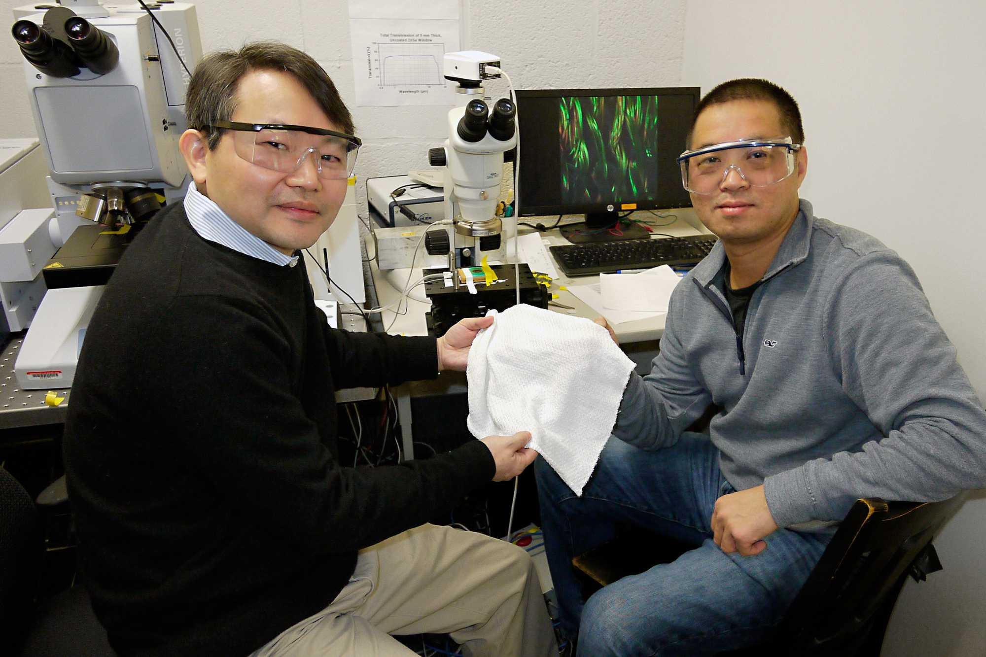 Professor für Chemie und Biochemie an der Universität von Maryland YuHuang Wang (links) and Physik Professor Min Ouyang halten ein Stück ihres neu entwickelten Stoffes. Er passt sich automatisch an die Körperwärme seines Trägers an.