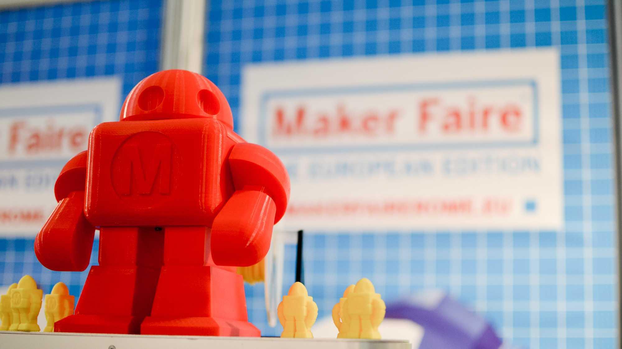 """Ein roter Roboter Makey aus dem 3D-Drucker, im Hintergrund der Schriftzug """"Maker Faire""""."""