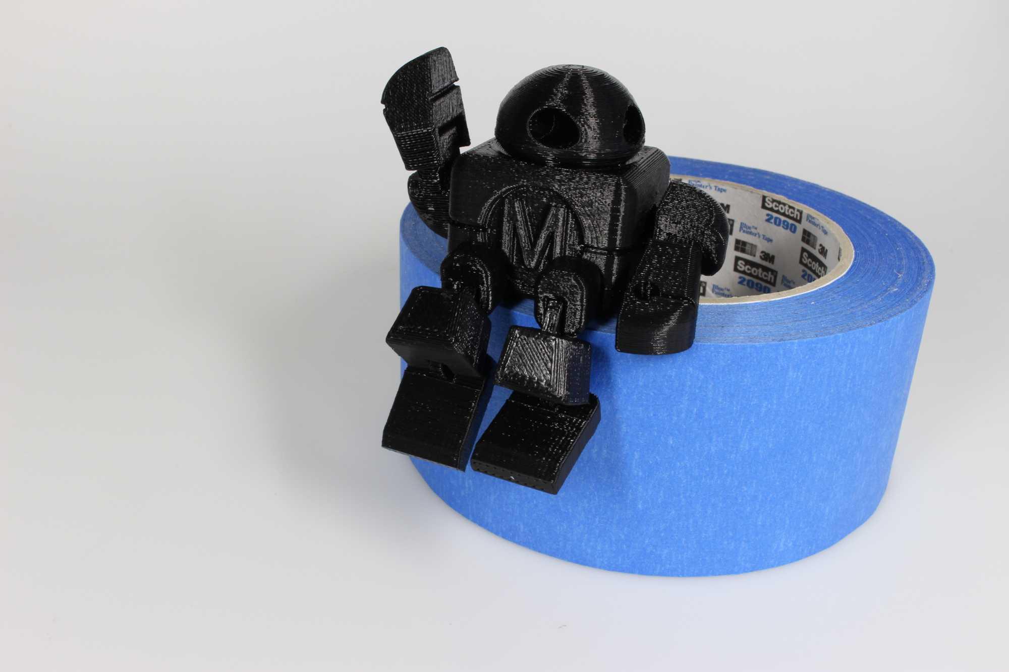 Ein schwarzer Roboter sitzt auf einer Rolle schwarzen Klebebands.