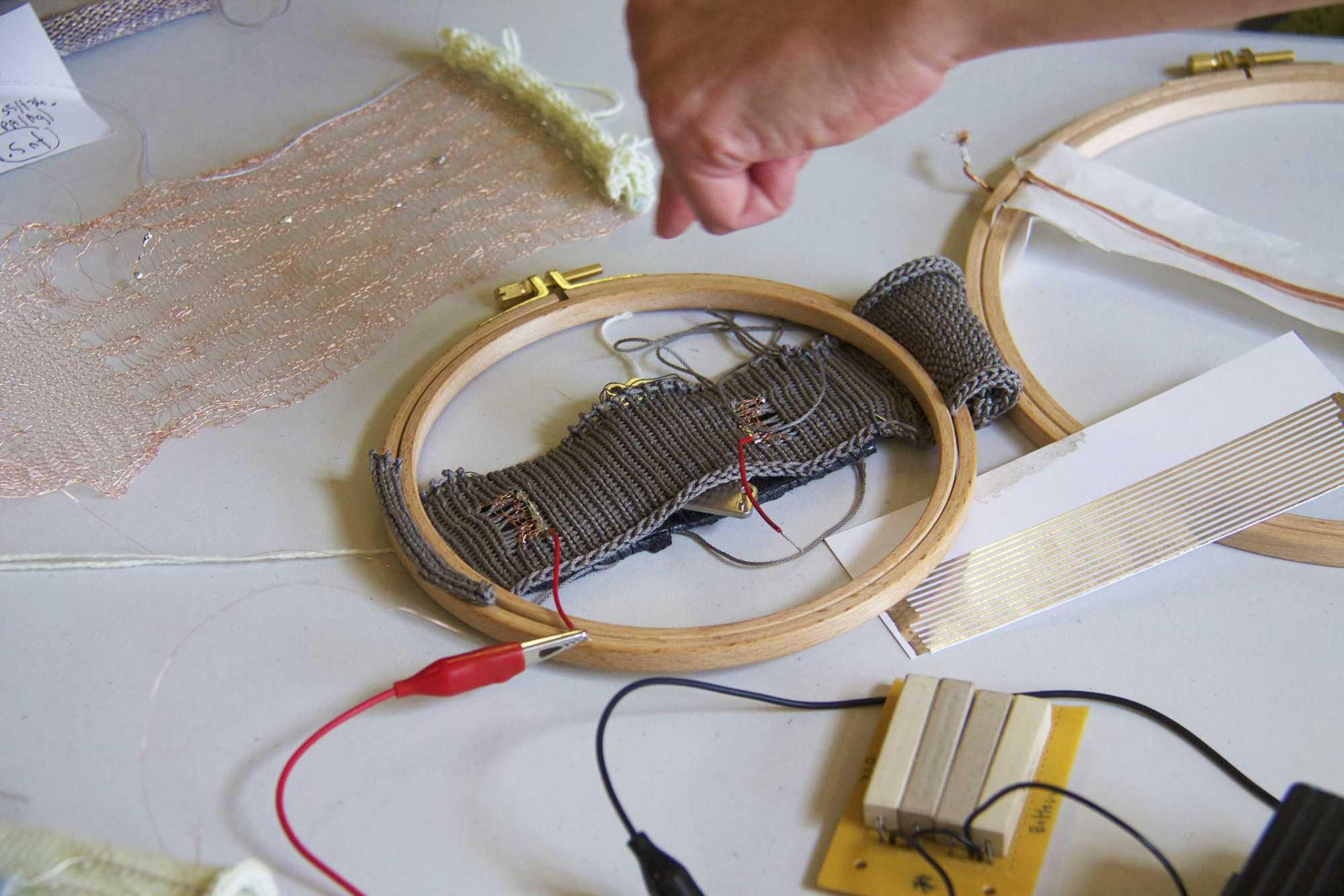 Ein runder Stickrahmen, in den ein Elektronikprojekt auf grauem Strick eingespannt ist.