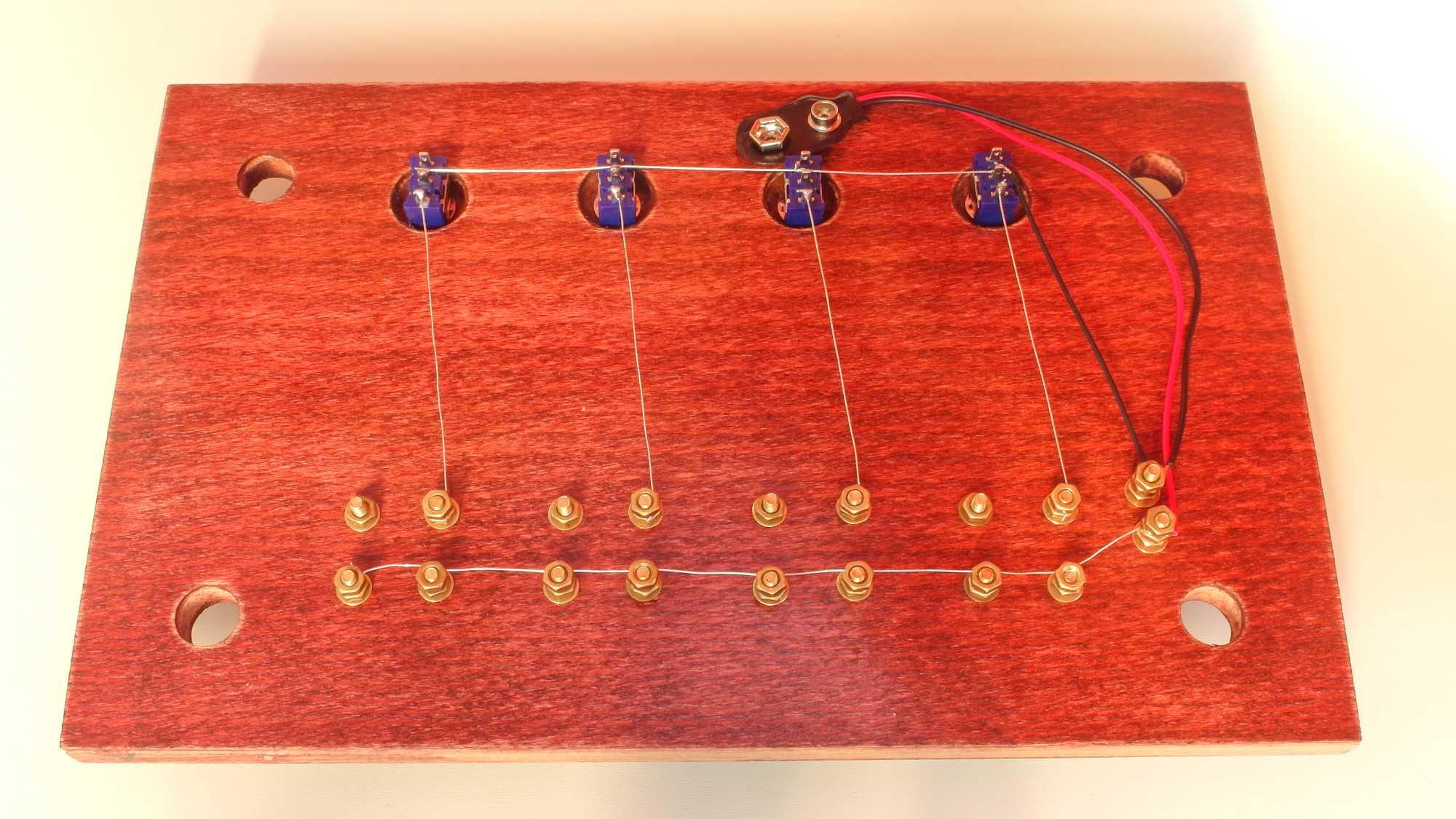 Unterseite des magischen Schaltpults: Ein Schaltkreis führt vom Batteriefach zu vier Glühbirnen-Anschlüssen, dann jeweils weiter zu vier Schaltern und zurück zur Batterie.