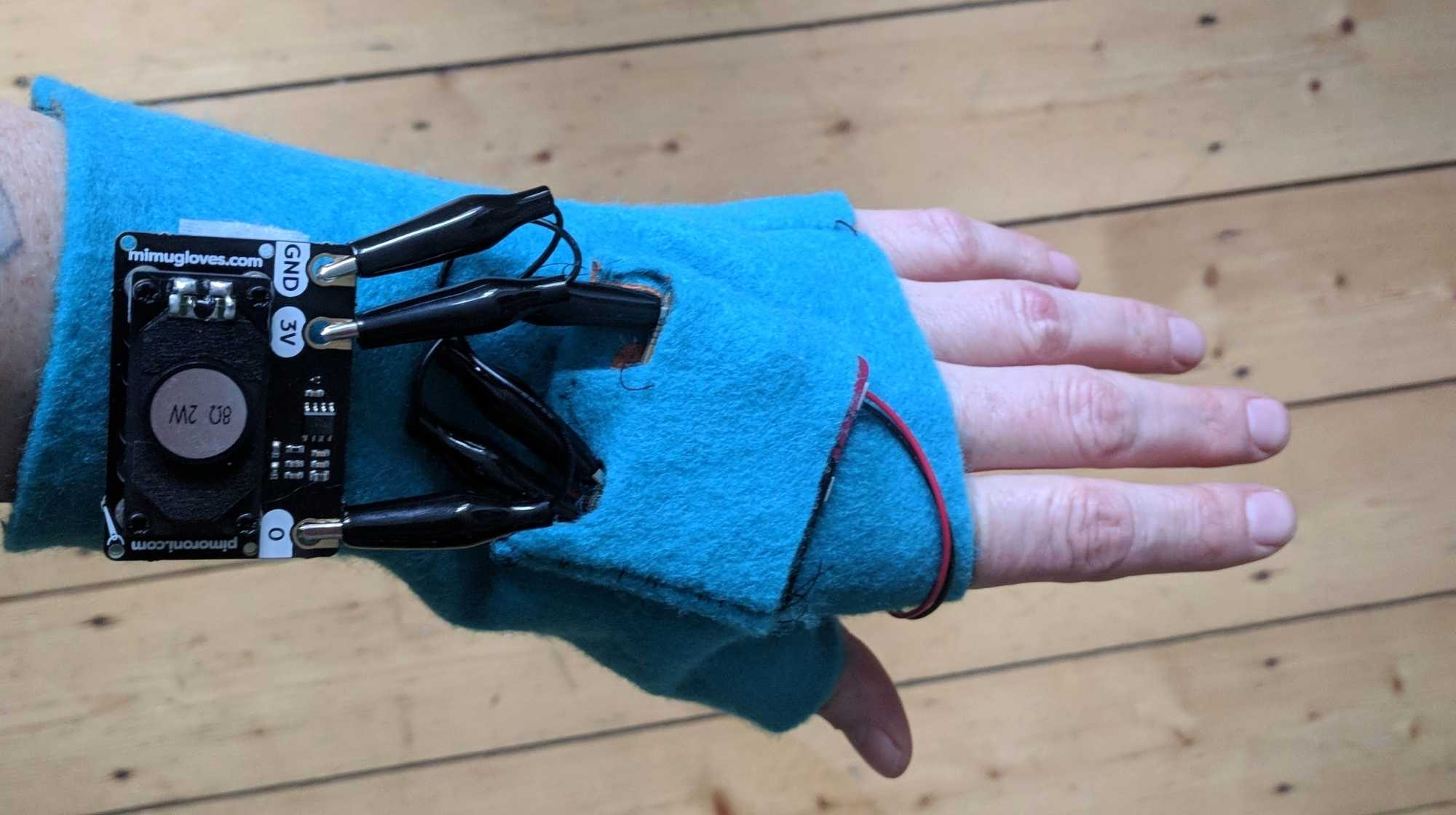 Eine Hand hält einen Handschuh mit aufgenähter Elektronik.