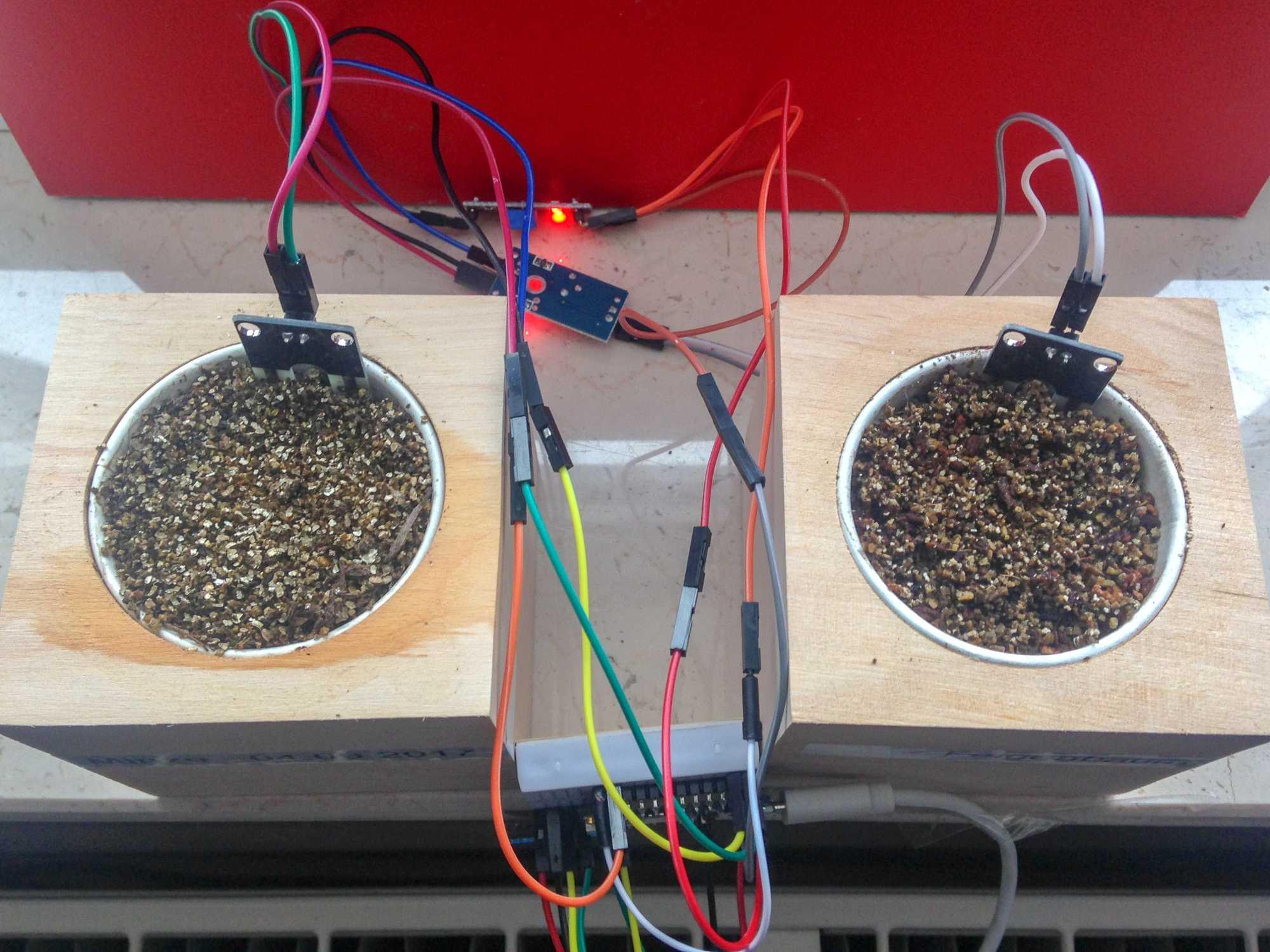 Zwei Blumentöpfe mit Feuchtigkeitssensor und angeschlossener Elektronik.