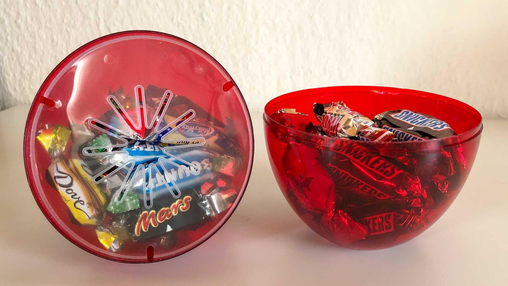 Geöffnetes Celebrations-Ei mit Süßigkeiten gefüllt.