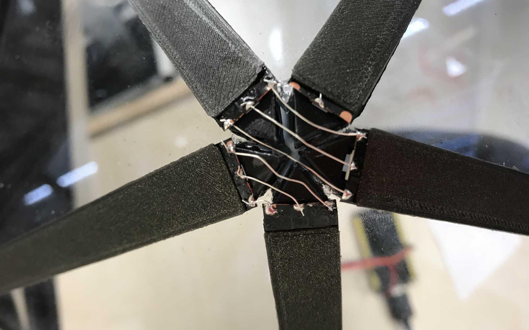 Fünf 3D-gedruckte Streifen treffen aufeinander, darüber ragen Drahtstreifen.