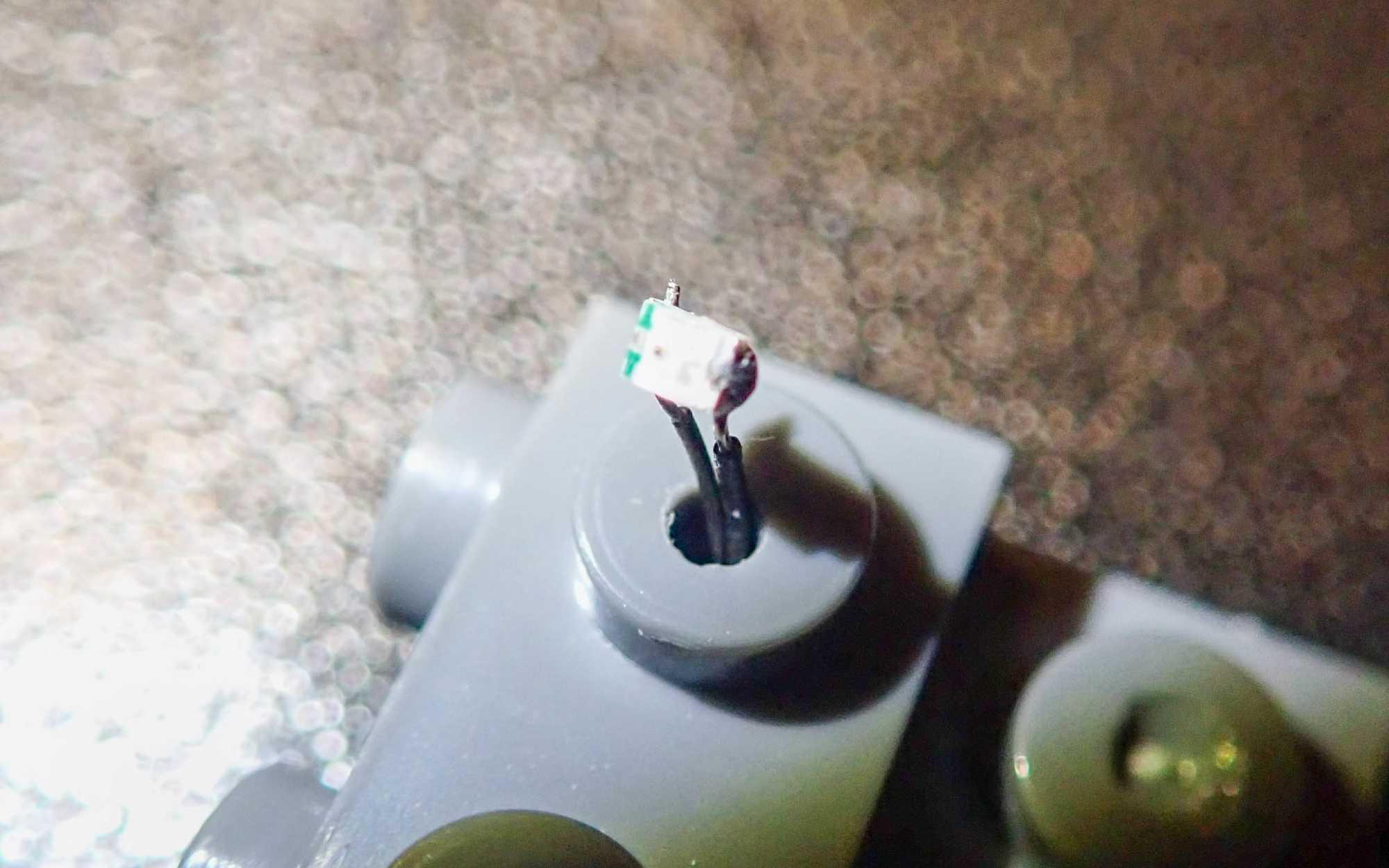 Aus einem aufgebohrten Legonoppen ragt eine kleine LED.