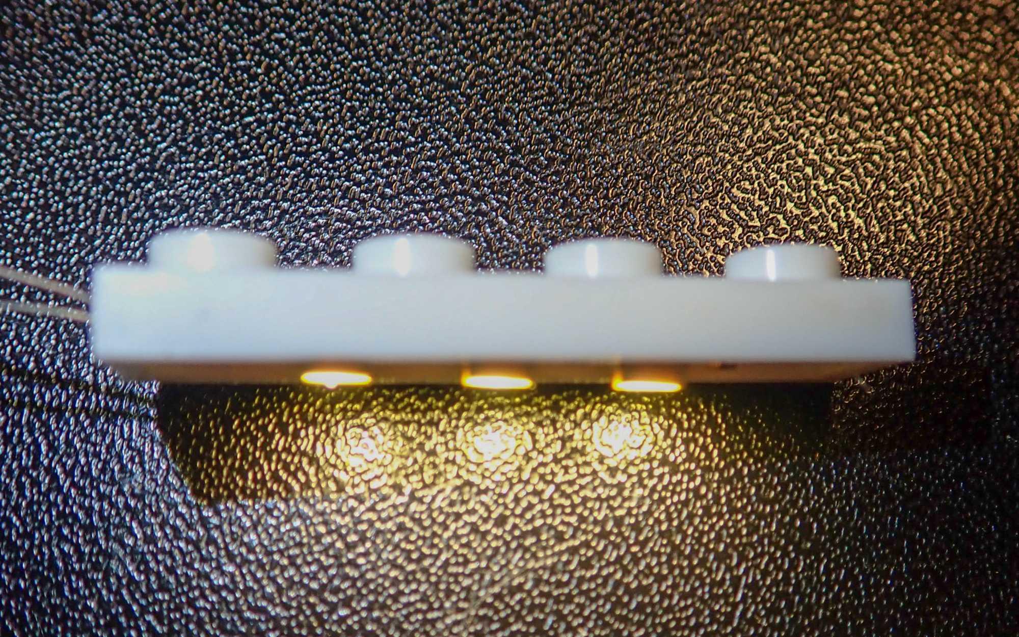 Ein weißer Lego-Streifen mit vier Noppen, auf der Unterseite sind drei LEDs befestigt.