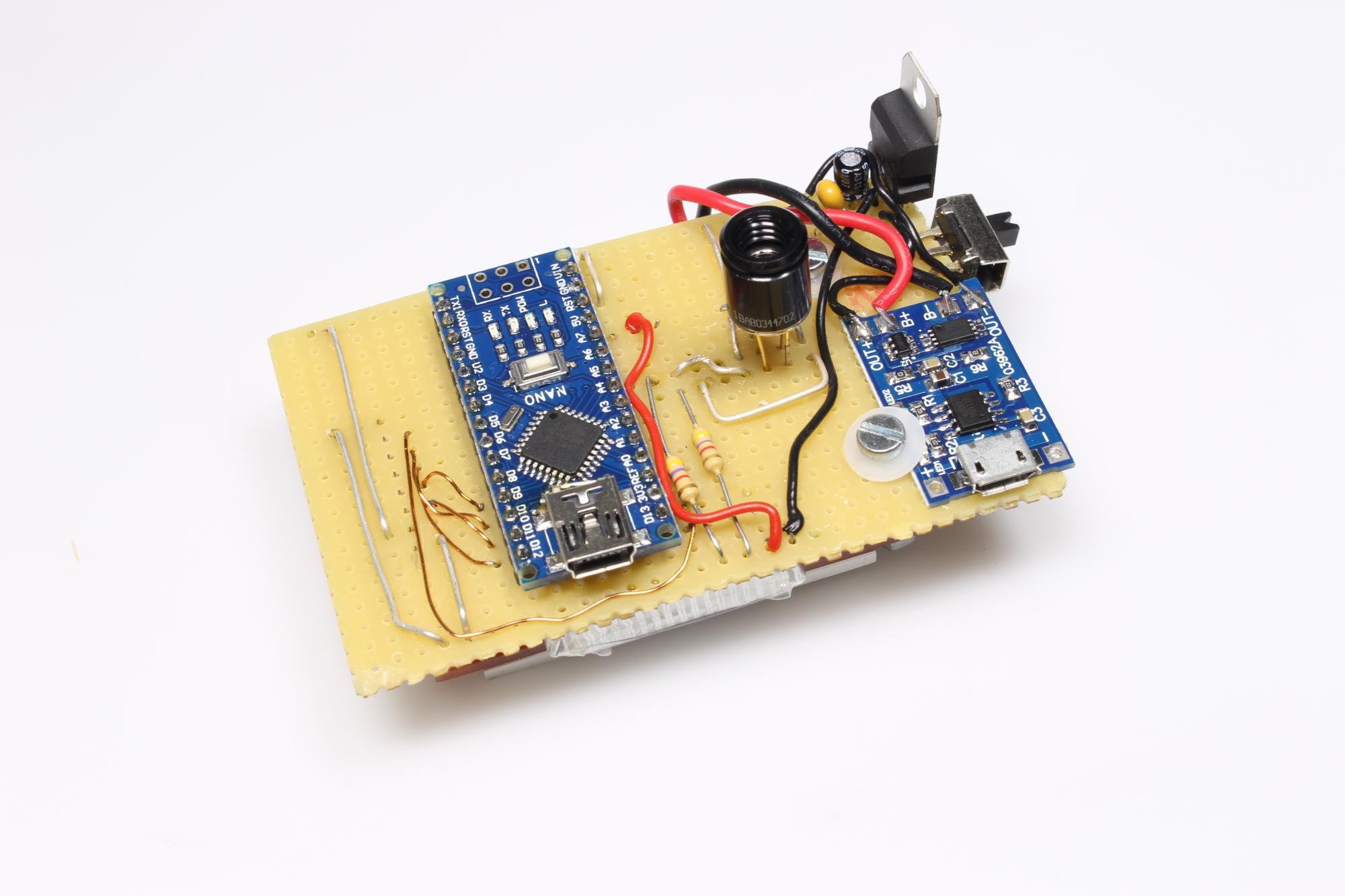 Gelbe Lochrasterplatine von vorn mit einem blauen Arduino Nano, schwarzen Infrarotsensor und blauem LiPo-Lademodul sowie weiteren elektrischen Bauteilen