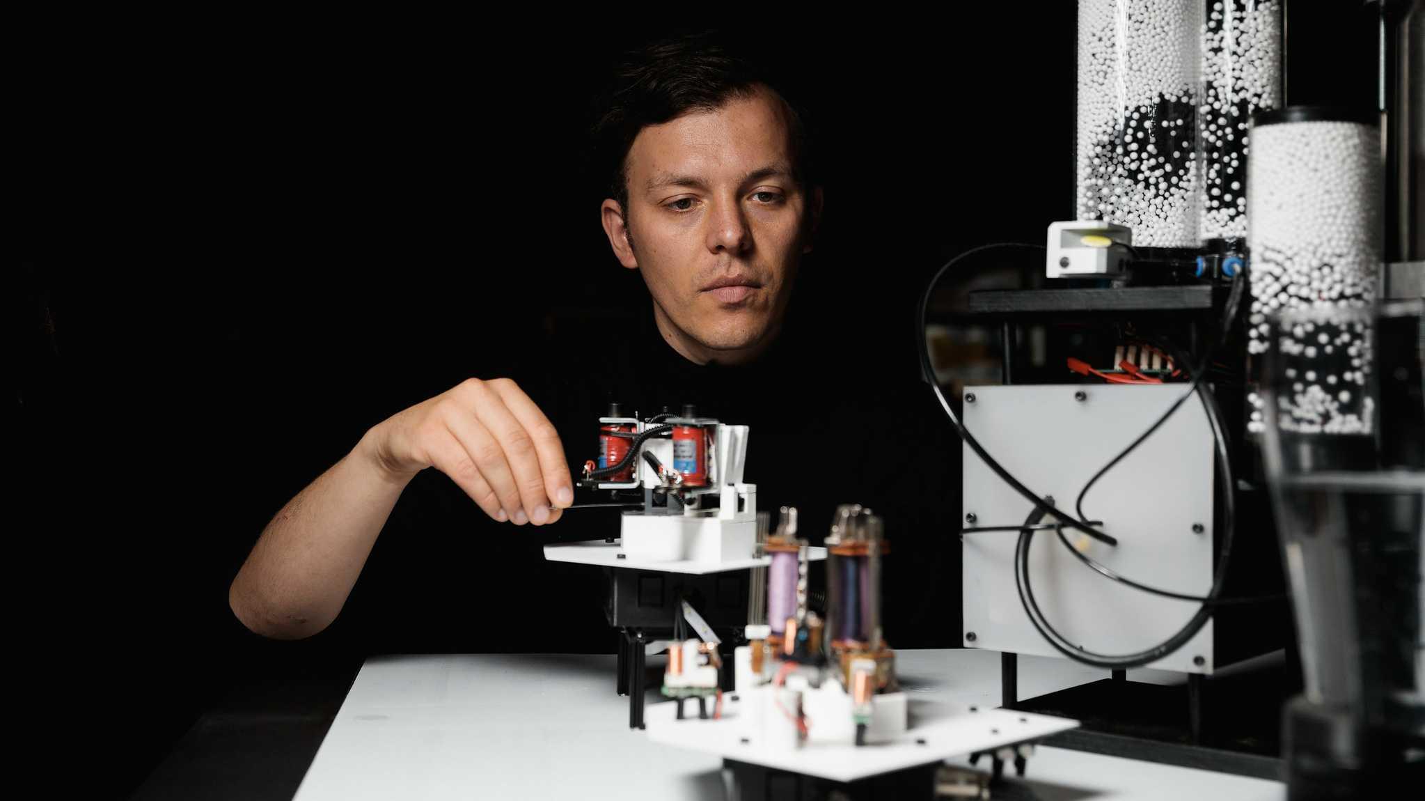 Ein weißer Mann schaut auf eine Maschine mit elektronischen Bauteilen und weißen Papierkügelchen in durchsichtigen Zylindern.