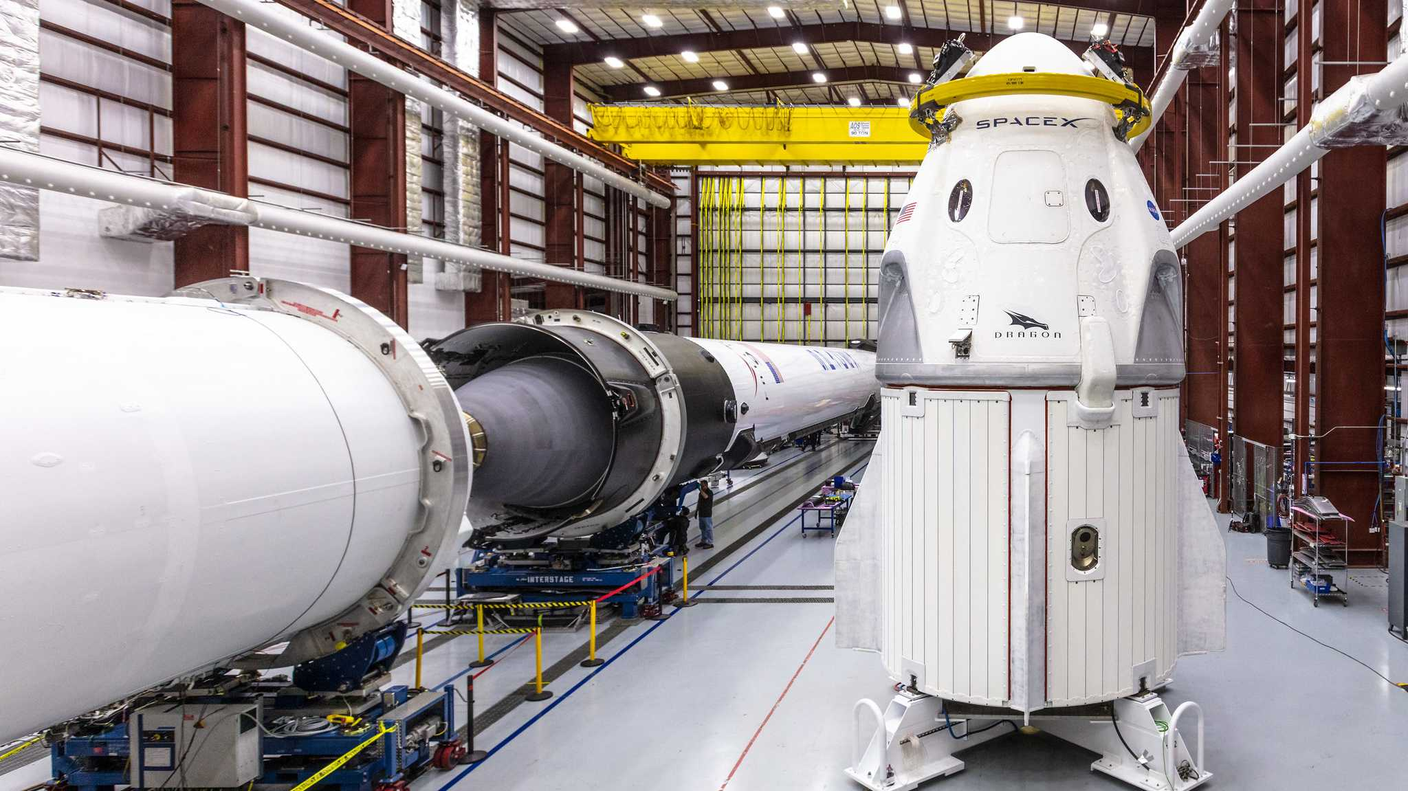 Links liegen Raketenteile, rechts steht der Crew Dragon in einem Hangar