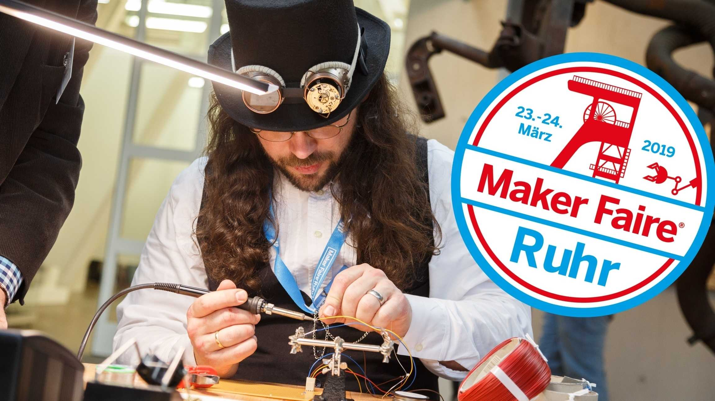 Ein Steampunker mit langen Locken und Hut mit aufgesetzter Retro-Brille lötet an einem Tisch.