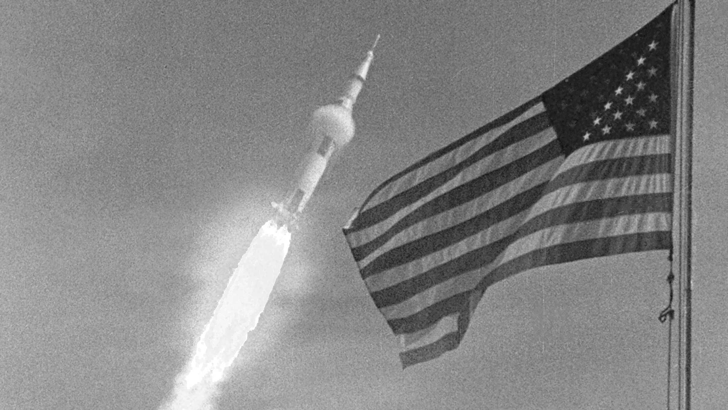Apollo-11-Rakete beim Start nebst US-Flagge