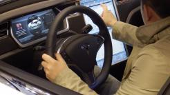 Ein Messebesucher nimmt das Cockpit des Tesla S in Augenschein.