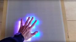 Eine Hand auf einem weißen Ikea-Lack-Tisch. Unter der Hand leuchten LEDs in pink und blau