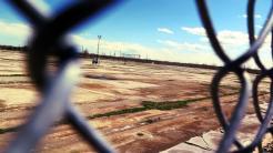 Großer Parkplatz ohne Autos, fotografiert durch Maschendrahtzaun