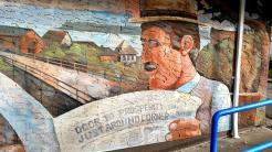 """Wandgemälde; Mann liest Zeitung mit Schlagzeile """"Prosperity just around corner, says mayor"""""""